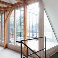 Wohnraum mit Aussicht auf Terrasse und Gewächshaus